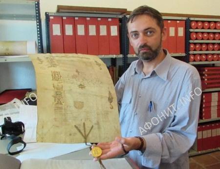 Сергея Шумило показывает оригинал грамоты царя Ивана Грозного Афонскому монастырю Хиландарь